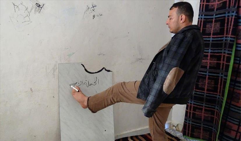 صورة عطّار..معلم بلا يدين ينير مستقبل طلابه بأنامل قدميه