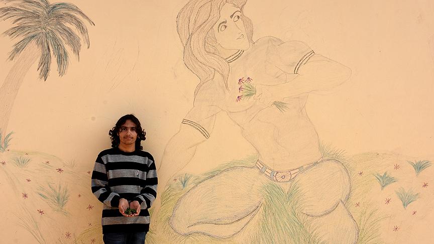 صورة شاب سوري معاق يرسم بألوان يستخرجها من الطين والفحم والحجر