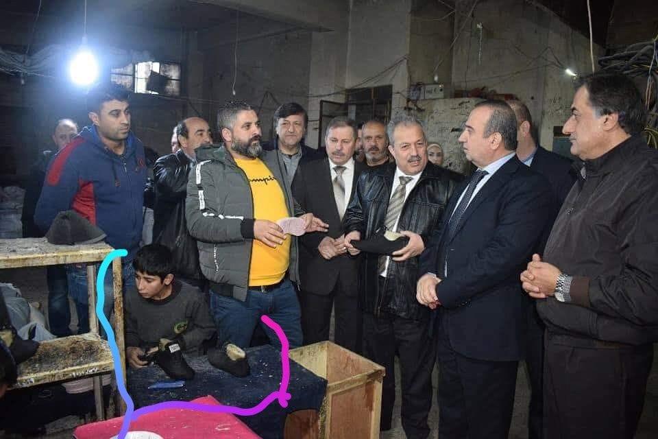 صورة دولة الأسد.. 3 وزراء ومحافظ يتفقدون ورشة أحذية يديرها طفل!