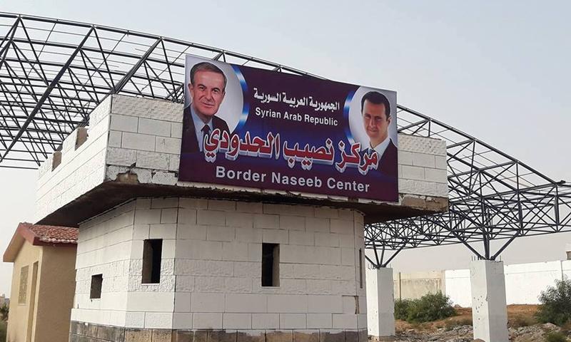 صورة مسلحون موالون للنظام ينتزعون صورة الأسد ووالده من معبر نصيب الحدودي